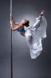 Sexig dansare som behagfullt vänder runt om pol Royaltyfria Bilder