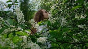 Sexig europeisk flickamodell som poserar på kamera, i att blomstra hägget, ultrarapid En kvinna med långt frodigt hår är arkivfilmer