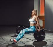 Sexig europeisk idrotts- konditionflicka som utarbetar i idrottshall Konditionkvinnan sitter på skivstång eller lutar på skivstån Arkivfoton