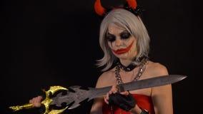 Sexig förförisk jäkel som flickan gör manikyr, snitt, spikar vid svärdet, firar halloween med läskiga roliga pumpor i mörker stock video