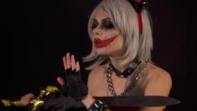 Sexig förförisk jäkel som flickan gör manikyr, snitt, spikar vid svärdet, firar halloween med läskiga roliga pumpor i mörker arkivfilmer