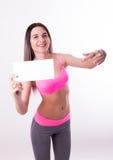 Sexig fitnesbrunett i en träningsoverall som rymmer det tomma vita brädet Royaltyfri Bild