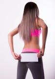 Sexig fitnesbrunett i en träningsoverall som rymmer det tomma vita brädet Fotografering för Bildbyråer