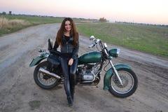 Sexig flicka för cyklist som sitter på den beställnings- motorcykeln för tappning Utomhus- livsstil tonad stående royaltyfri bild