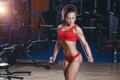 Sexig flicka för kondition med det sunda sportiga diagramet med överhopprepet i idrottshall royaltyfria bilder