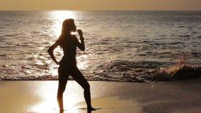 sexig flicka för mystisk kontur på stranden under solnedgång lager videofilmer