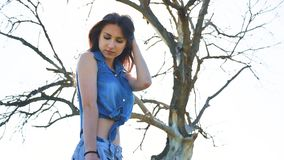 sexig flicka Flickakvinnaanseende på naturen i kortslutningar och skjortan på bakgrund av den torra trädsolljusnaturen stock video