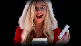 Sexig flicka i den santa dräkten som öppnar en gåva lager videofilmer