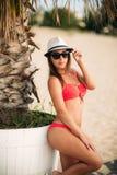 Sexig flicka i en rosa baddräkt på stranden Arkivbild