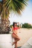Sexig flicka i en rosa baddräkt på stranden Sommar soligt väder  Arkivbild
