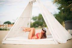 Sexig flicka i en rosa baddräkt på stranden Sommar soligt väder Arkivfoton