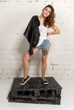 Sexig flicka i kortslutningar och ett svart omslagsanseende på paletter Vit tegelstenvägg som inte isoleras Royaltyfri Fotografi