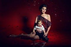 Sexig flicka i röd kort klänning med ett pojkebarn Royaltyfri Fotografi