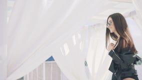 Sexig flicka i svart och solglasögon som poserar nära havet i den vita gazeboen 4K arkivfilmer