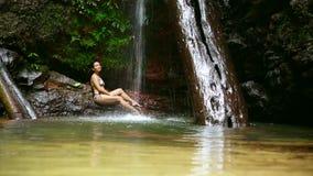 sexig flicka med bikinin som ner ligger i vattenfallfloden arkivfilmer