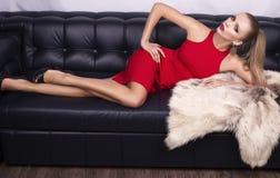 Sexig flicka med blont hår i röd klänning med päls Arkivbild