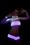 Sexig flicka med glödsmink i ultraviolett lampa Arkivbild