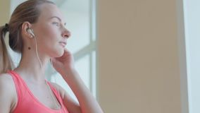 Sexig flicka med hörlurar som kopplar av i idrottshallen lager videofilmer