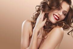 Sexig flicka med långt och skinande krabbt hår Härlig modell, lockig frisyr på orange bakgrund Royaltyfria Foton