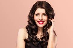 Sexig flicka med långt och skinande krabbt hår Härlig modell, lockig frisyr på orange bakgrund Royaltyfria Bilder
