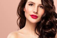 Sexig flicka med långt och skinande krabbt hår Härlig modell, lockig frisyr på orange bakgrund Fotografering för Bildbyråer