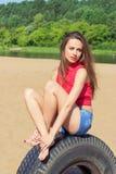 Sexig flicka med långt sammanträde för mörkt hår i kortslutningar på stranden på hjulet på en solig dag Arkivbilder