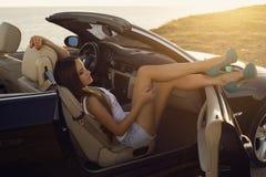 Sexig flicka med mörkt hår som poserar i lyxig cabriolet på solnedgångkust fotografering för bildbyråer