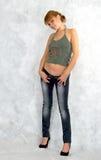 Sexig flicka som försöker på jeans. Arkivfoton