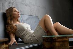 Sexig flicka som kopplar av på den trevliga soffan i studio