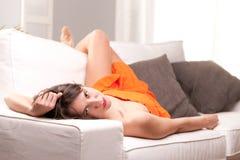 Sexig flicka som ligger slappt på en soffa som stirrar på kameran royaltyfri bild