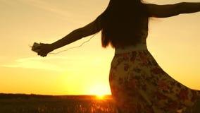 Sexig flicka som lyssnar till musik och dansar i str?lar av en h?rlig solnedg?ng mot himlen ung flicka i h?rlurar och lager videofilmer