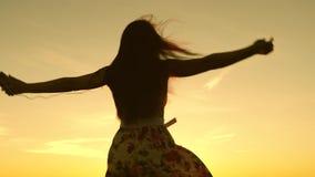 Sexig flicka som lyssnar till musik och dansar i str?lar av en h?rlig solnedg?ng mot himlen ung flicka i h?rlurar och stock video