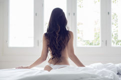 Sexig flickabaksida på en säng Arkivbild