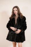 Sexig flickablondin i svart päls Arkivfoton