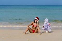 Sexig flickajultomten i bikini på ett strandgran-träd Arkivbild