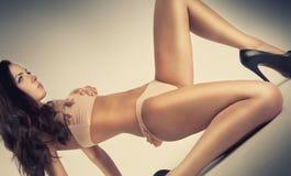Sexig glamour poserar flickan som ligger på golv Fotografering för Bildbyråer