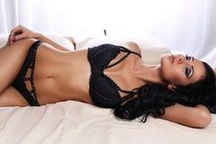 Sexig glamourkvinna med mörkt hår som bär elegant svart damunderkläder Fotografering för Bildbyråer