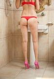 Sexig härlig kroppfors av den unga kvinnan som bär röd damunderkläder och höga häl i badrum Kvinnakropp med långa ben Royaltyfri Foto