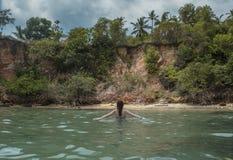 Sexig härlig kvinna i bikini som går i havet på den tropiska stranden royaltyfri foto