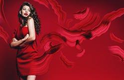 Sexig härlig kvinna i röd klänning med röda penseldrag Arkivbild
