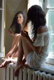 Sexig härlig kvinna som ser till spegeln på fönstret Arkivfoton
