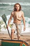 Sexig halv naken man med åran i fartyg på stranden royaltyfri foto