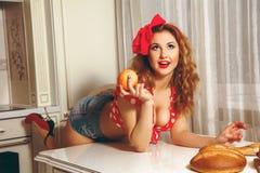 Sexig hausewife för ung dam med lockigt hår och trevlig makeup i stift Fotografering för Bildbyråer