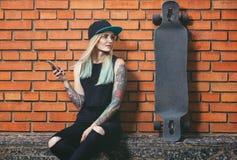 sexig hipsterflicka i tatuering mot en vägg för röd tegelsten med ett långt bräde Arkivbilder