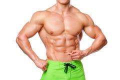 Sexig idrotts- man som visar buk- muskler utan fett som isoleras över vit bakgrund Muskulös manlig konditionmodellabs Arkivfoto