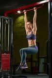 Sexig konditionflicka som gör handtag upp på horisontalstång i idrottshall Muskulös kvinna, abs, format buk- royaltyfri fotografi
