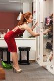 Sexig krökning för asiatisk kvinna som ser till garderobshopping Arkivbild