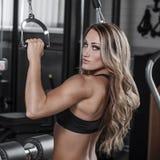 Sexig kroppsbyggarepulldownövning i idrottshall Arkivfoto