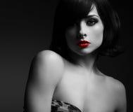 Sexig kvinna för kort hår med röda kanter i mörker svart white Arkivbild