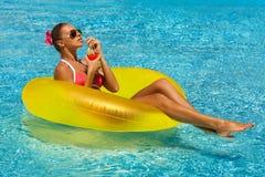Sexig kvinna i bikini som tycker om sommarsolen och garvar under ferier i pöl med en coctail